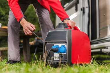 Caucasian Men in His 40s Firing Up Gas Powered Portable Inverter Generator To Connect Electricity To His Camper Van.