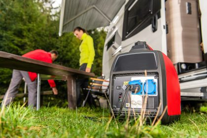 Modern Gasoline Powered Generator Running Next to Camper Van Recreational Vehicle. Powering RV Camping Pitch with Own Energy Source.